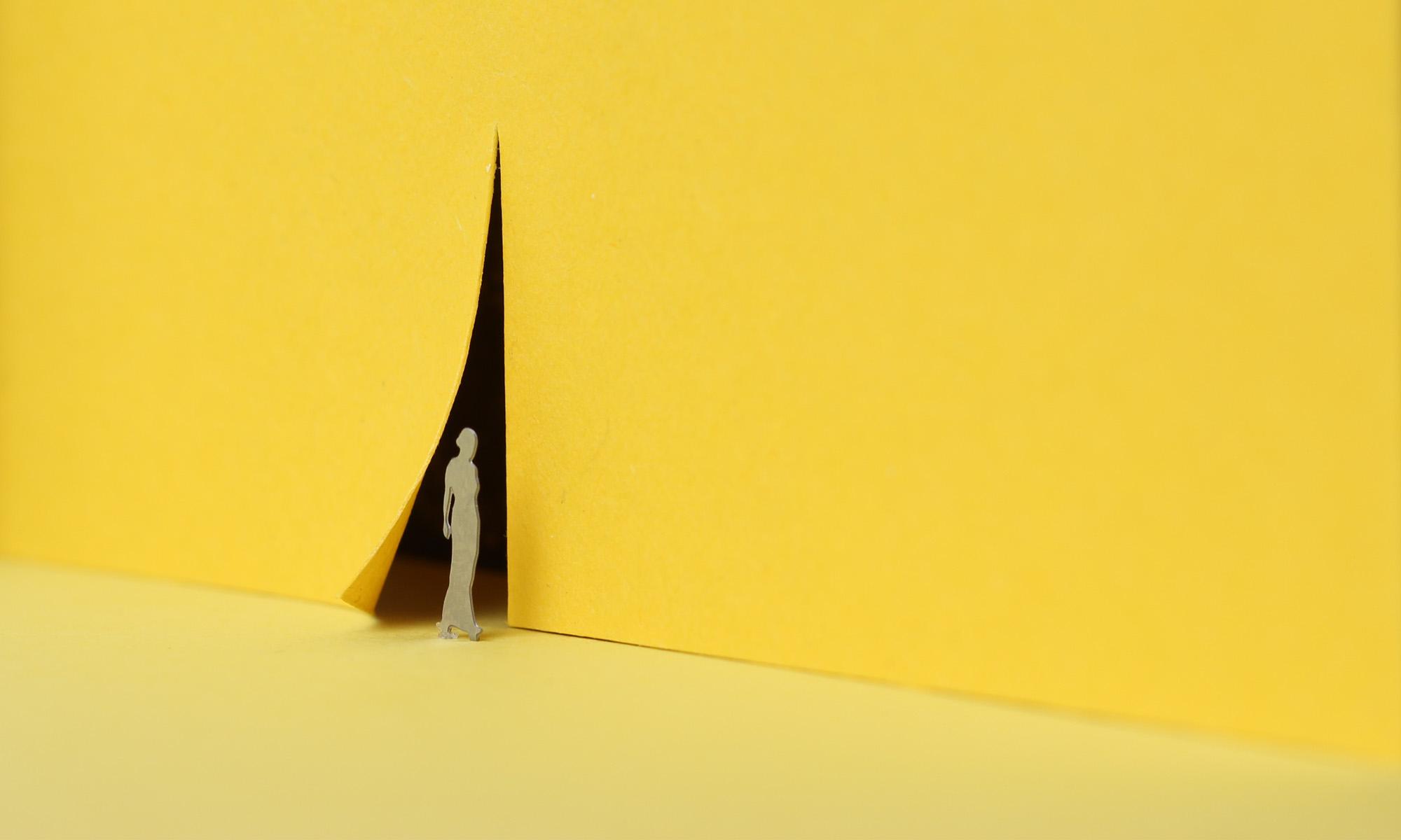 Siluette einer Frau vor gelber Wand. Fotografie von Andrea Blaschke